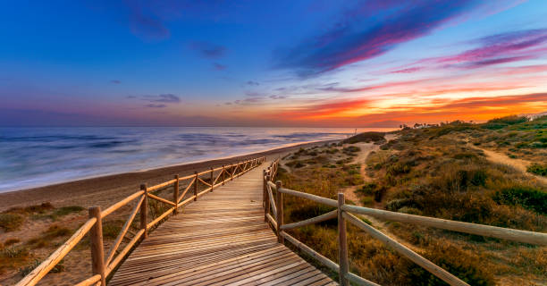Bright sunset sky over sea and timber path stock photo