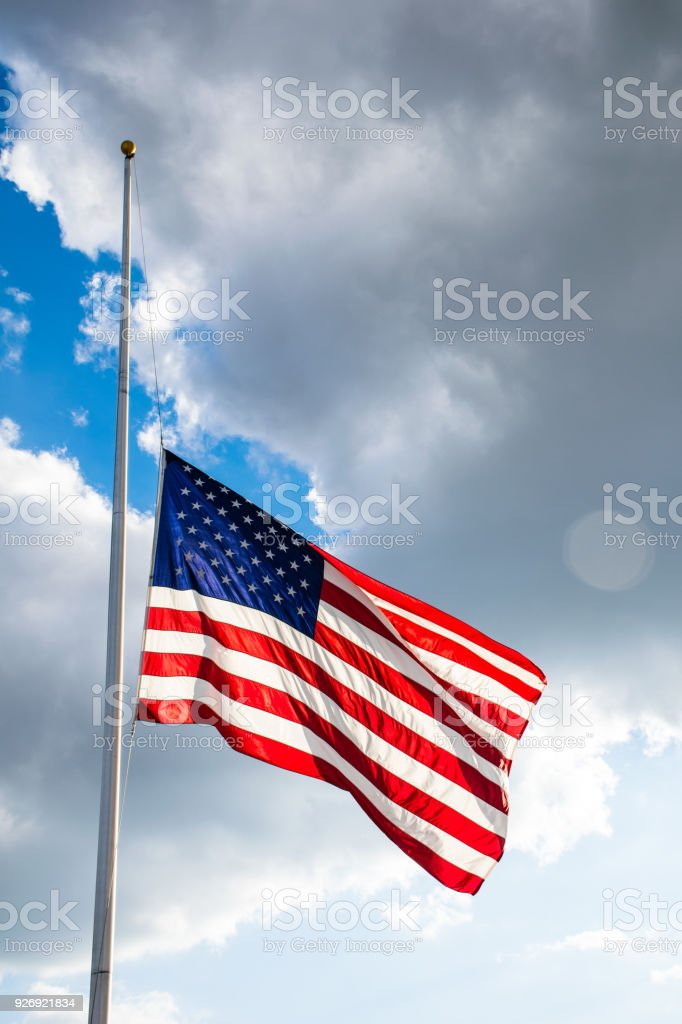 Bright sunshine illuminates the Perfect American Flag lowered to Half-Mast waving in the wind fully extended stock photo