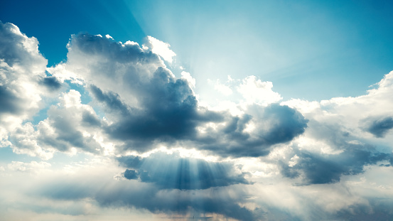 Bright rays of sunshine peer through cloudscapes against a blue clear sky