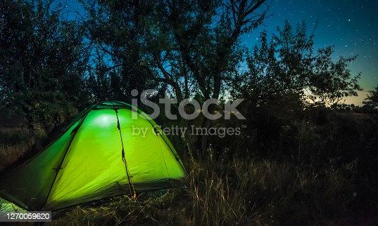 Bright illuminated tourist tent under amazing night starry sky