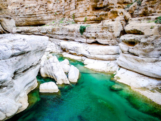 Bright, turquoise blue waters of Wadi Shab, a canyon near Muscat in Oman Bright, turquoise blue waters of Wadi Shab, a canyon near Muscat in Oman riverbed stock pictures, royalty-free photos & images