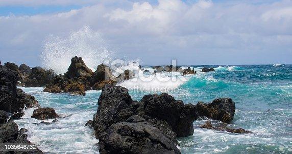 Bright turquoise wave crashes on black lava coastline in Hawaii