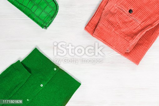 1078252326 istock photo Bright warm clothing. Fashion clothes for womans. Pink pants from corduroy, green jumper and hand bag on wooden desk with copy space. Top view. Flat lay. 1171501826