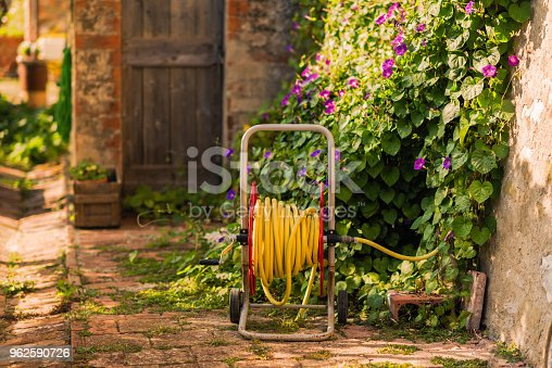 Yellow Bright watering garden hose near old stone house