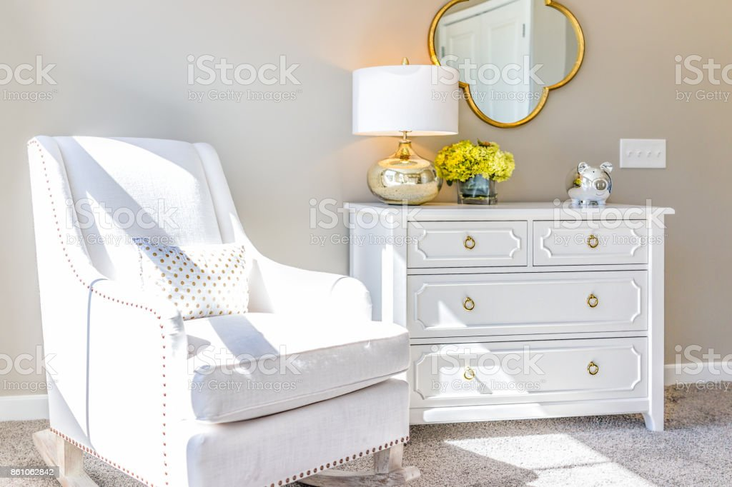 Bright white modern rocking chair in nursery room with chest of drawers, decorations in model staging home, apartment or house stock photo