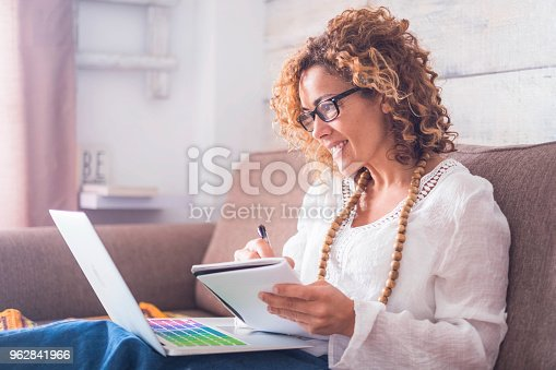 bright window light image for caucasian beautiful middle age woman working at home with laptop and notebook. writing a note on the book with a pen like old style but use internet on the computer