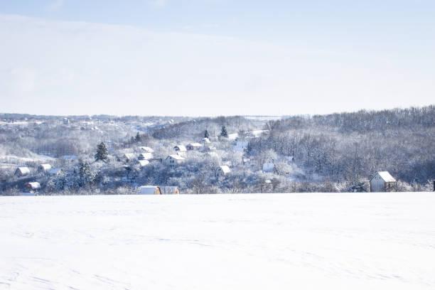 bright winter village under a blue sky stock photo