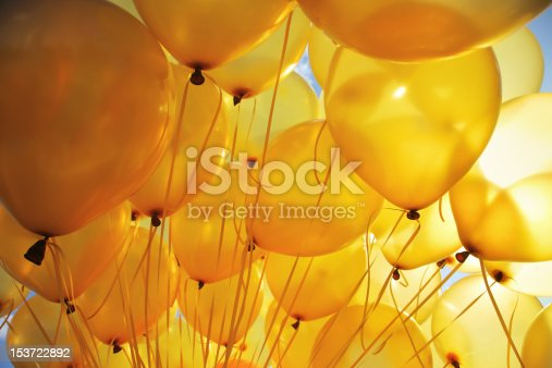 Background of bright yellow inflatable balloons up in the air, backlit by sun.