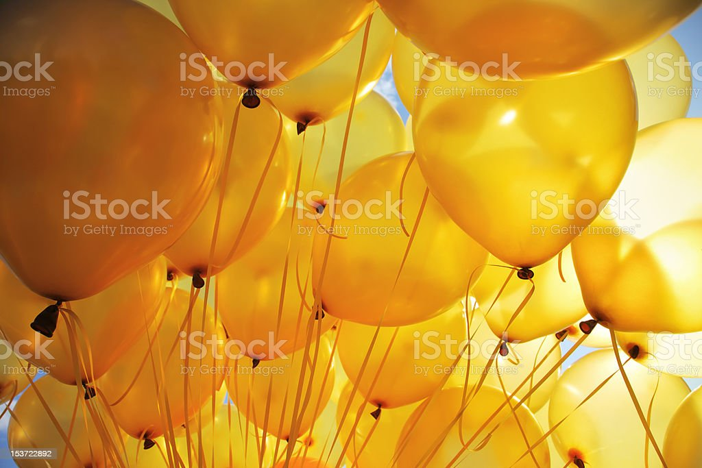 Bright yellow balloons backlit in sky background stock photo