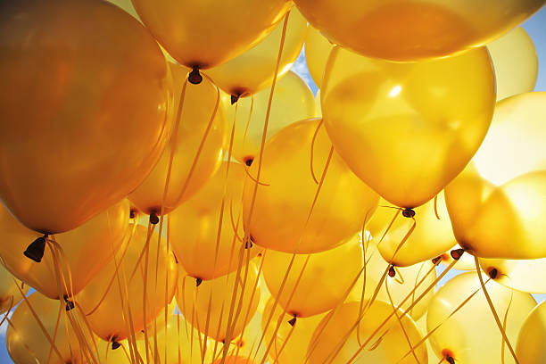 bright yellow balloons backlit in sky background - yellow stock photos and pictures