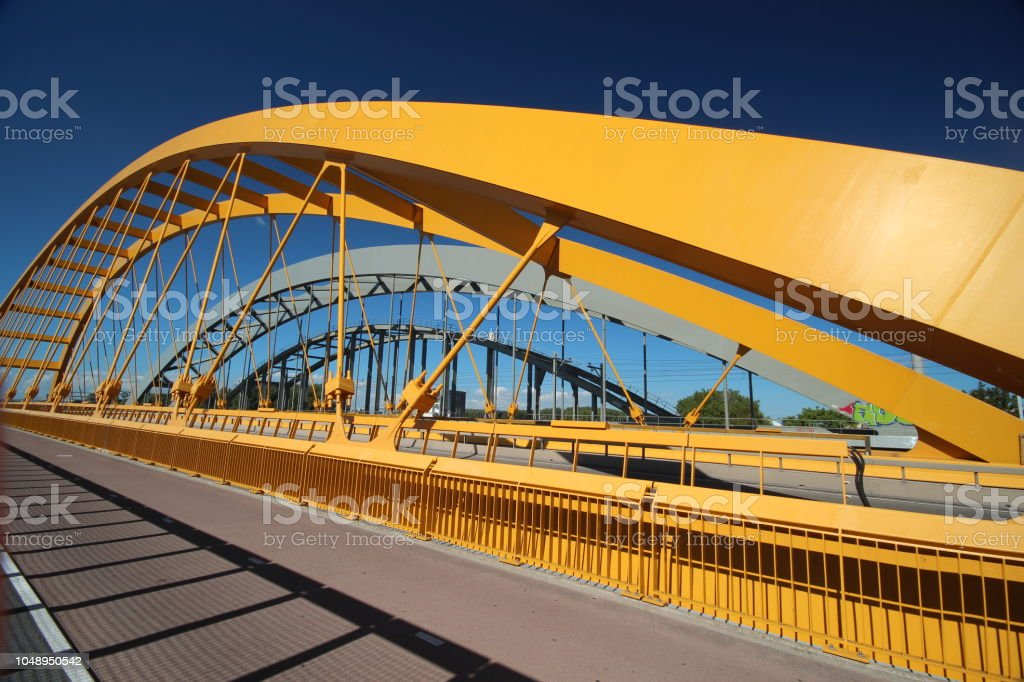 Heldere gele brug genaamd Hogeweidebrug over het Amsterdam-Rijnkanaal in Utrecht voor verkeers- en Vleutenspoorbrug die een trainbridge foto