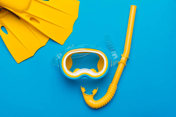 Bright yellow flippers and diving mask on a vibrant backround Bright yellow flippers and diving mask on a vibrant backround snorkel stock pictures, royalty-free photos & images