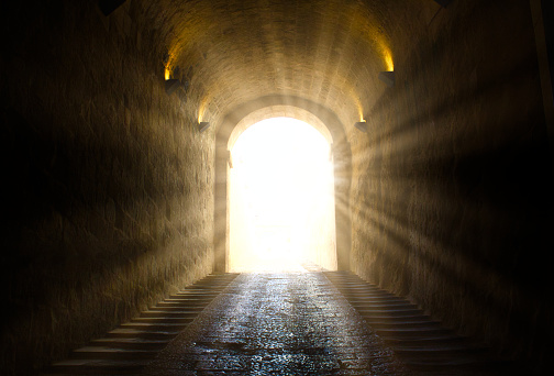 A bright yellow glowing light breaking through at the end of a dark tunnel