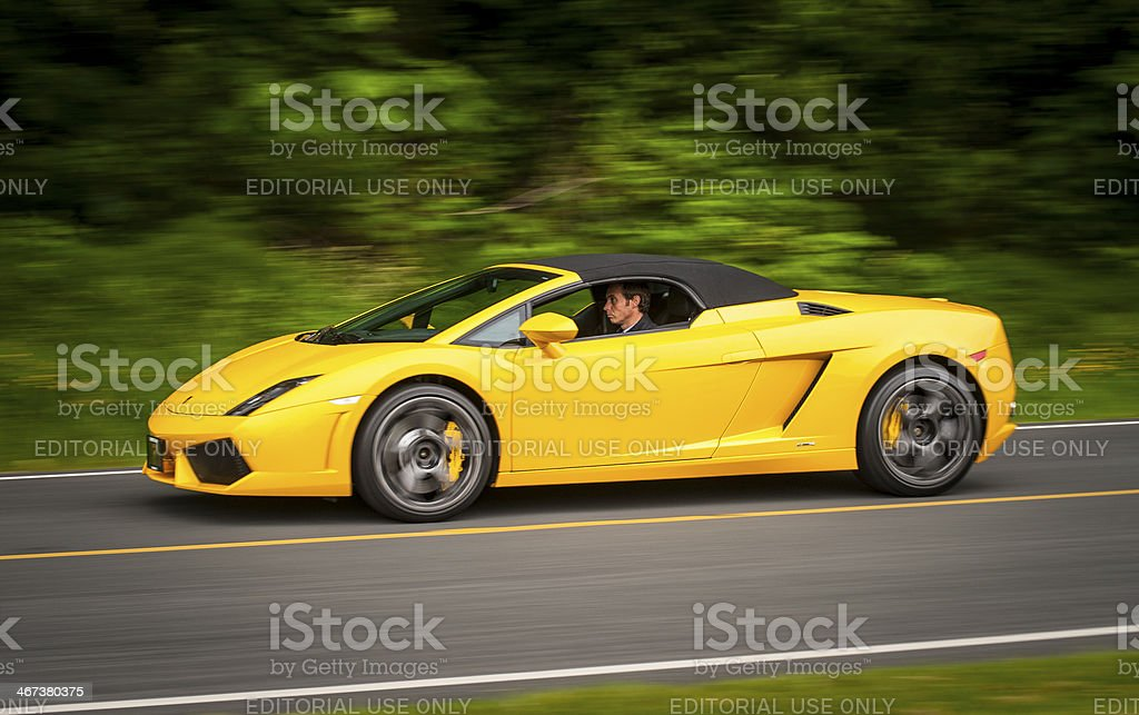 Bright yellow Lamborghini Gallardo driving on road. stock photo