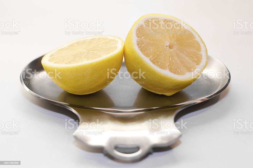 Bright yellow lemon on a silver dish royalty-free stock photo