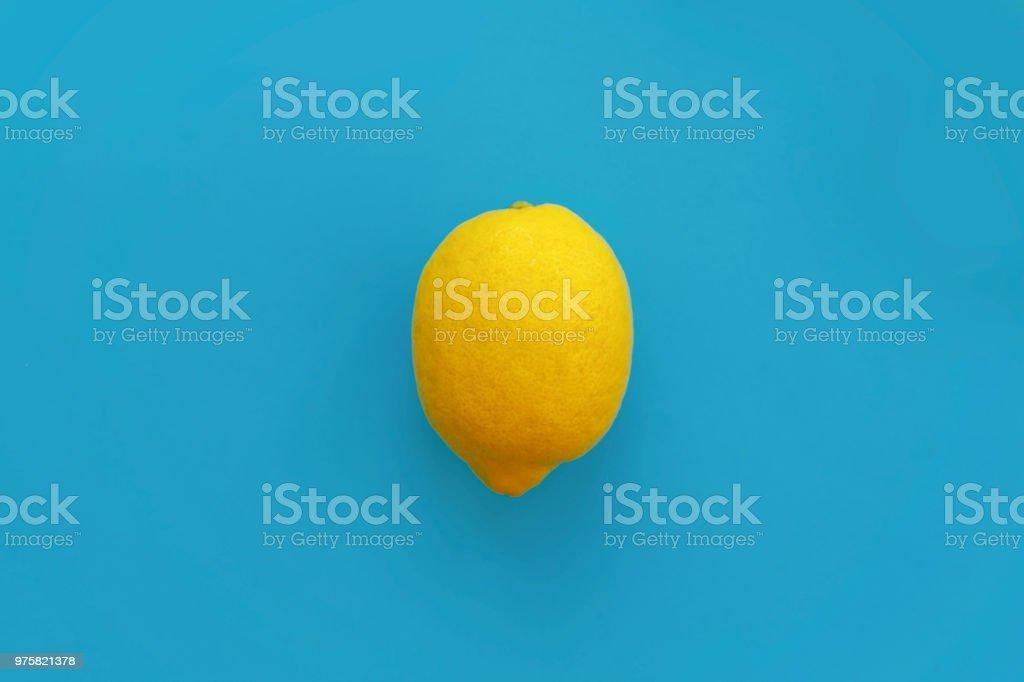 leuchtend gelbe Zitrone auf blauem Papier flach zu legen. trendige stilvolle Hintergrund Obst Draufsicht. Platz für text - Lizenzfrei Abstrakt Stock-Foto