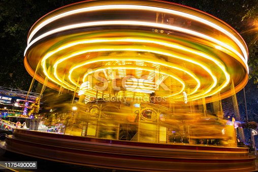 The bright lights of a fast moving fairground merry-go-round blur against a dark night sky. The motion blurred yellow lights are spinning underneath the rides carousel.