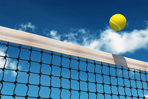 Bright yellow tennis ball going over net on a beautiful day stock photo