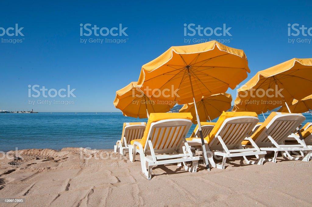 Bright yellow umbrellas on a sand beach stock photo