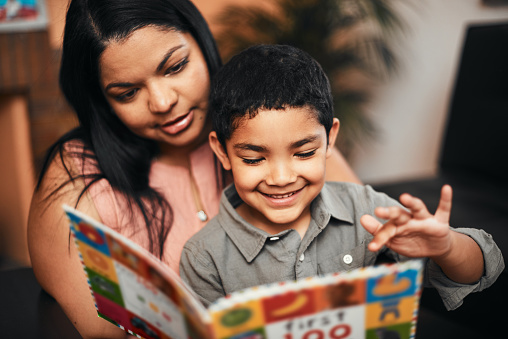 Shot of a mother and her little son reading a book together at home