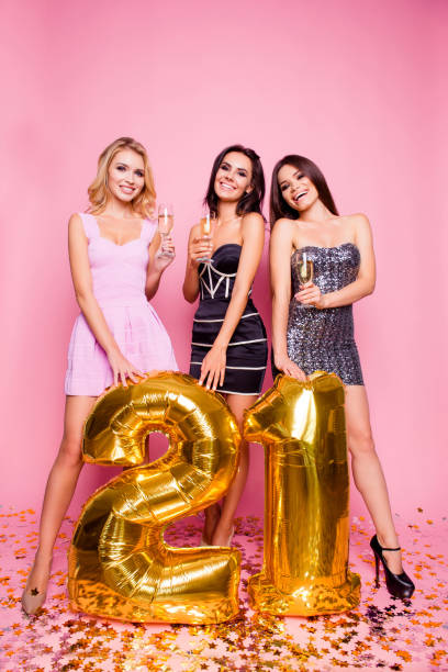brightful expressions of happy emotions of three amazing pretty astonished girls having fun  celebrating birthday party  21 years old in luxury dresses with golden baloons  standing over pink background - number 21 stock photos and pictures
