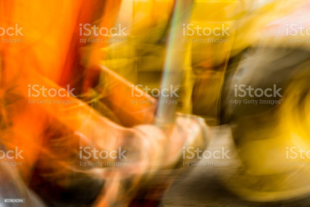 brightly colored artisticly blurred orange and yellow heavy equipment parts stock photo