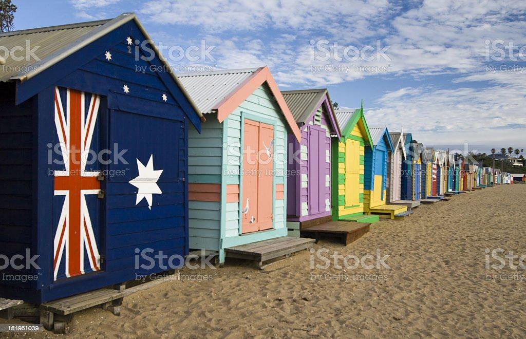 Brightly colored Brighton beach huts and sand stock photo