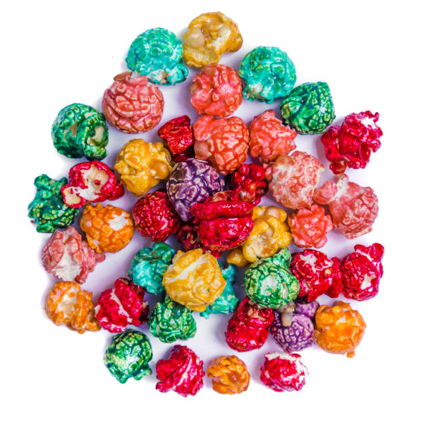 Brightly Colored Candied Popcorn, white background. Horizontal image of Junk food, fruit flavored popcorn in light pink bowl. Colorful, rainbow, candy coated popcorn. Shallow focus on popcorn in bowl. Isolated on white stock photo