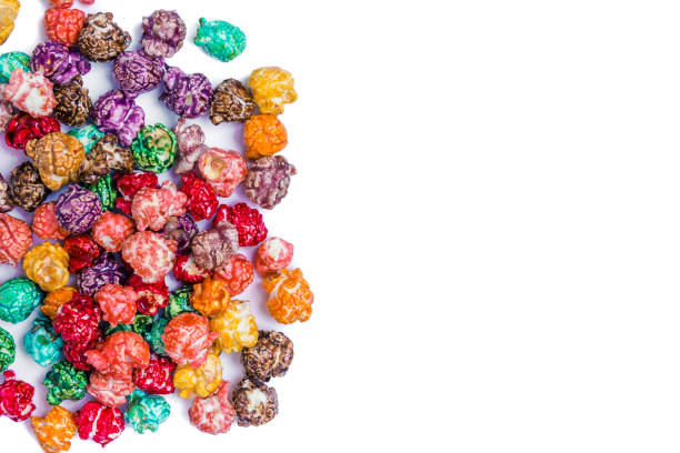 Brightly Colored Candied Popcorn, white background. Horizontal image of Junk food, fruit flavored popcorn. Colorful, rainbow, candy coated popcorn. Shallow focus on popcorn in bowl. Isolated on white selective focus and copyspace. stock photo
