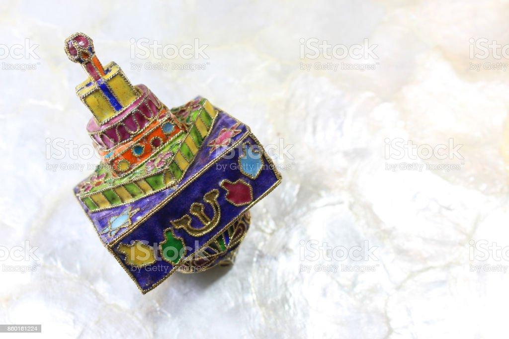 Brightly colored cloisonne Hanukkah dreidel on a soft white background stock photo