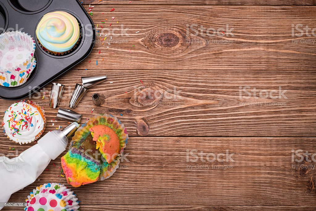 Brightly colored cupcakes on the wooden table. stock photo