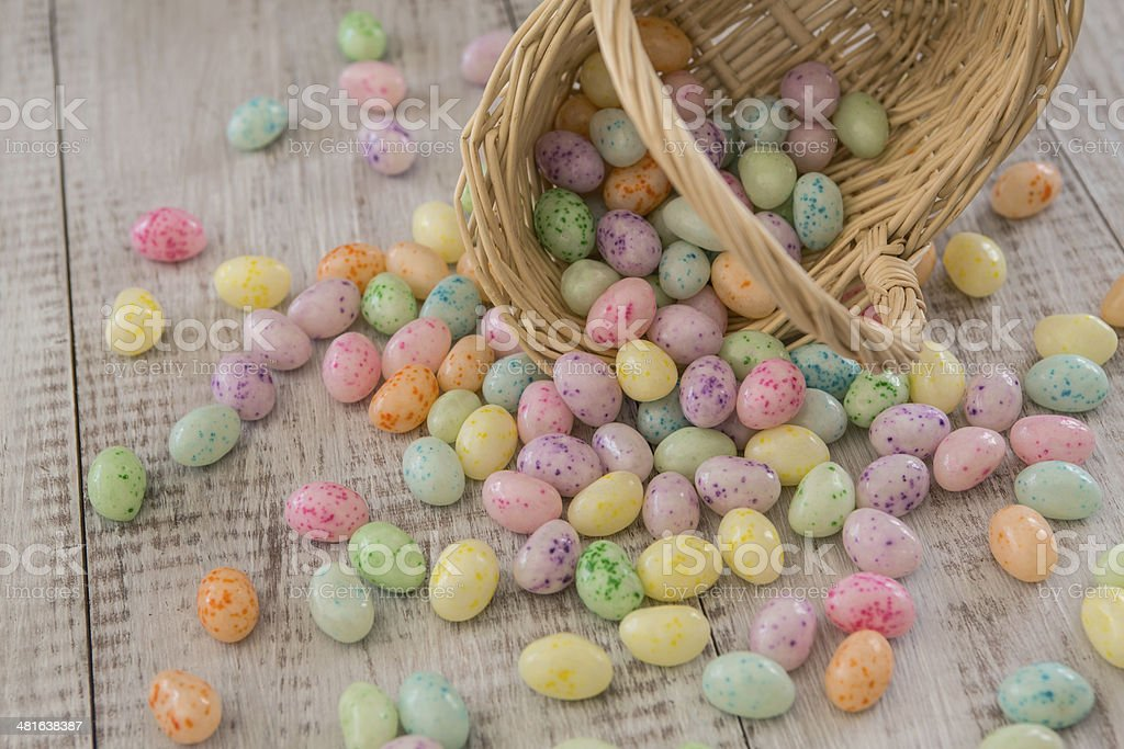 Brightly colored Easter Egg Candy spilling from wicker basket stock photo