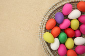 Brightly colored easter eggs, in a straw basket against a beige background.