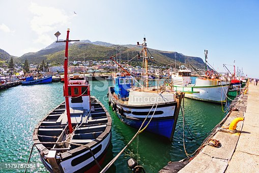 Tourists walk along the wharf alongside the famous fishing harbor of Kalk Bay.