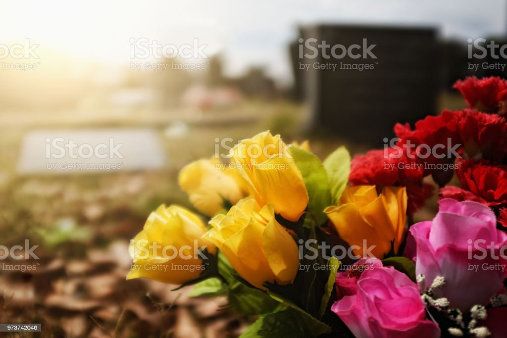 Brightly colored flowers on a grave stock photo