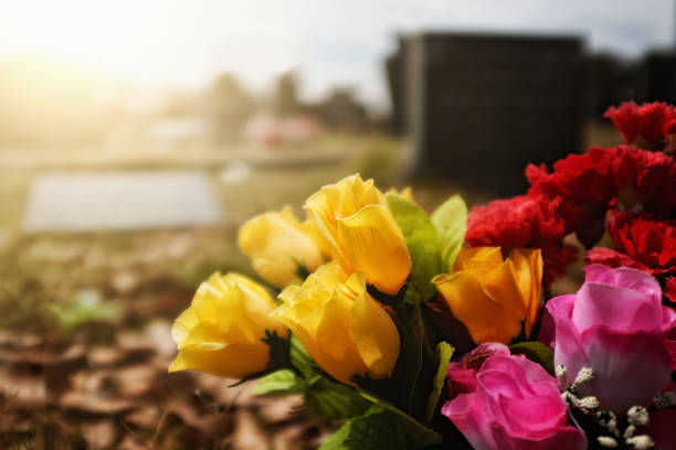 brightly colored flowers on a grave - cemetery stock photos and pictures