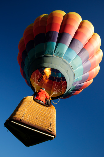 A brightly colored hot air balloon launching with its burner wide open