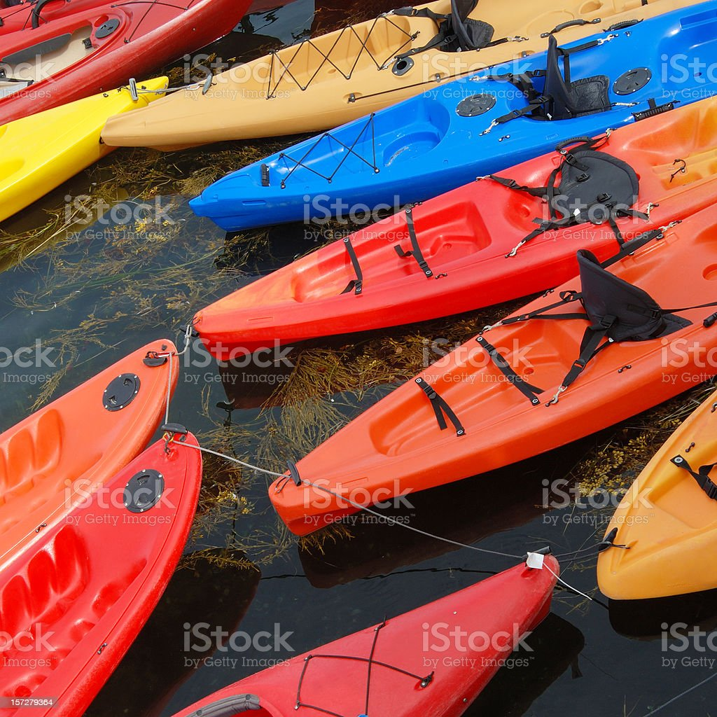 Brightly colored kayaks on water royalty-free stock photo