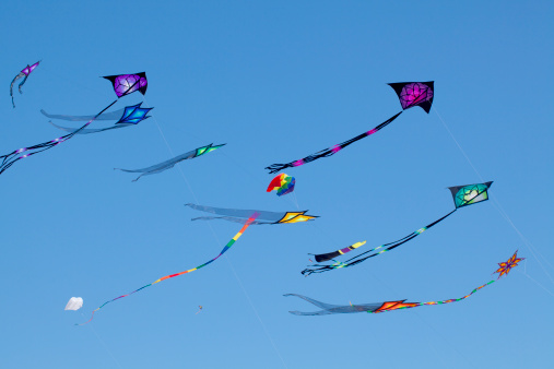 Brightly colored kites sailing against clear blue sky