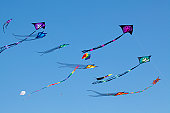 Variety of colorful Kites in a clear blue sky at the Wildwood Kite Festival in New Jersey