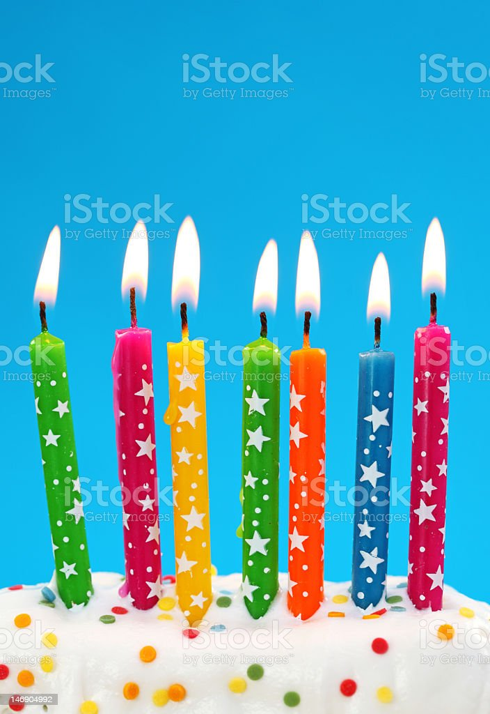 brightly colored lit birthday candles with stars on in cake stock