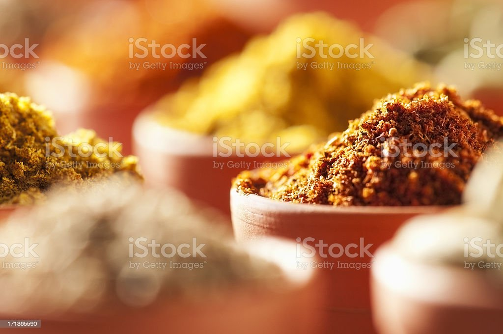 Brightly coloured ground cooking spices in terracotta bowls stock photo