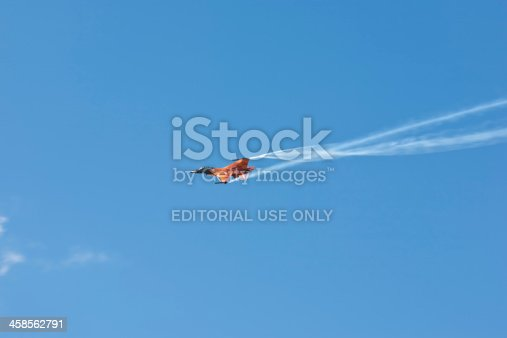 istock Brightly coloured orange F16 fighter jet against blue sky 458562791