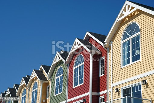 A newly constructed row of brightly coloured North American style town houses. Photographed in Summerside, Prince Edward Island, Canada.