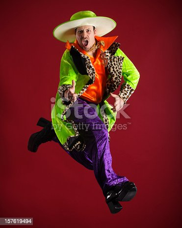A young man wearing brightly colored clothing in a mid-air pose against a red beckground.