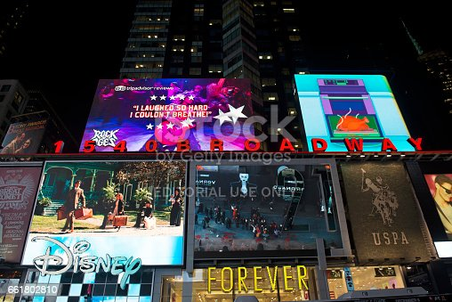 Times Square and the Broadway theatre district during night is one of the most visited places by locals and tourists. A large LCD screen is showing people in the street.