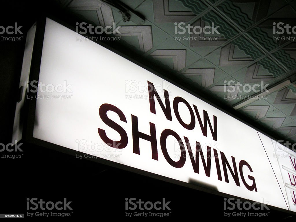 A brightly illuminated now showing sign glows at night stock photo
