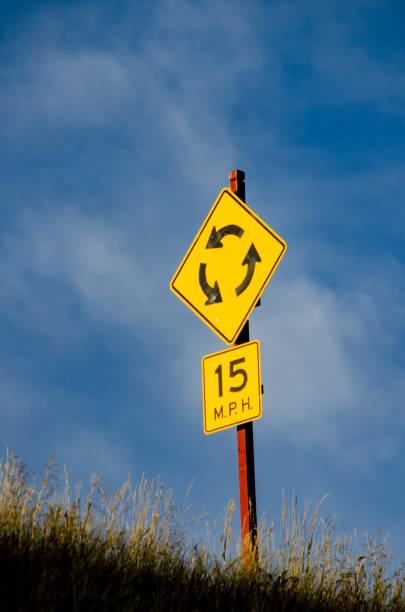 hell beleuchtetkreiskreisstraßenseitig über blauem himmel mit einem geposteten geschwindigkeitslimit von 15 mph - sich im kreis drehen stock-fotos und bilder