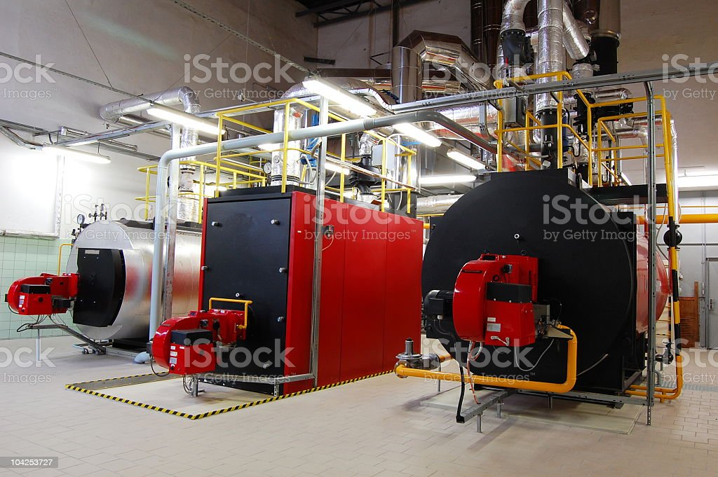 A brightly lit boiler room with red and black gas boilers stock photo