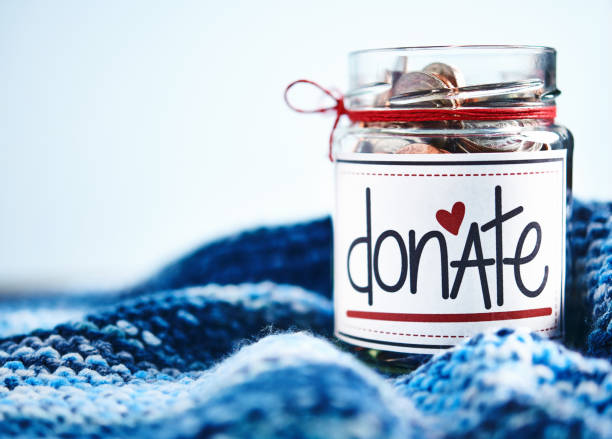 brightly lit donation money jar filled with coins - cassetta per le offerte foto e immagini stock